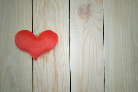Red heart on wooden background. Concept for Valentines Day or Wedding background. Banco de Imagens