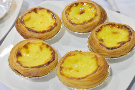 Egg tart with bread small cup and butter on white plate in the restaurant. Fast food for the working age and the people.