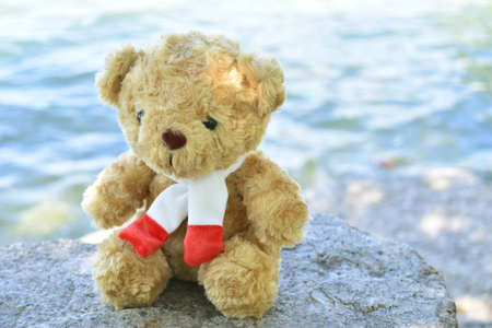Cute Teddy bear on old stone and sea background. Banco de Imagens