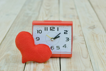 Concept alarm clock with red heart shape on wood board. Valentines Day background. Banco de Imagens