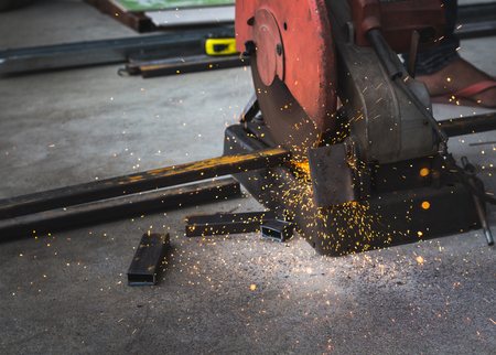 cutter: worker cutting iron tube with steel cutter