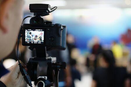 De media nemen video op tijdens de persconferentie. Journalisten zijn aan het interviewen, met de cameraman aan het opnemen Persbureaus komen samen om nieuws te maken.