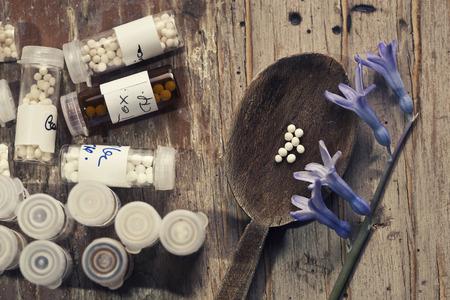 Homeopatía - Un concepto de la homeopatía con la medicina homeopática (azúcar / píldoras lactosa y sustancias homeopáticas líquidos) Foto de archivo