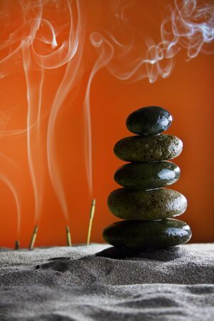 fulcrum: tower of stones and frankincense in the sand orange background