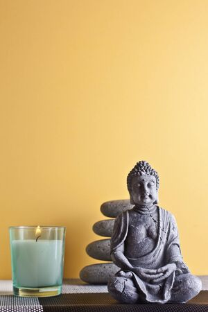 frankincense: stone sitting buddha and frankincense yellow background