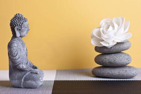 frankincense: stone sitting buddha and frankincense yellow background