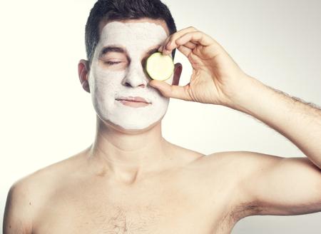 limpieza de cutis: apuesto hombre con máscara facial de arcilla en el spa de belleza y pepino