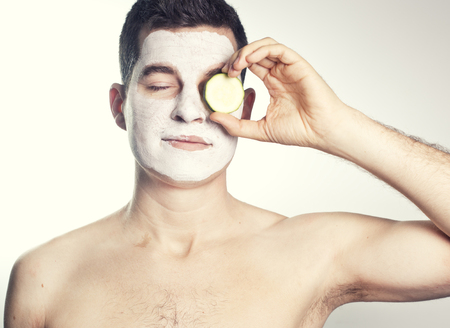 male facial: handsome man with clay facial mask in beauty spa and cucumber Stock Photo