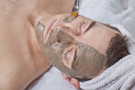 male facial: man receiving spa facial treatment, pencil and mud