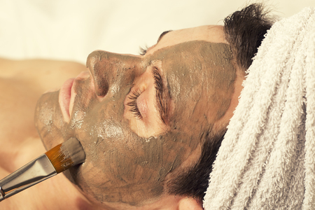 man receiving spa facial treatment, pencil and mud