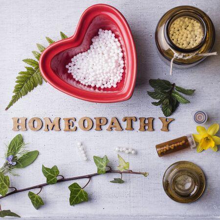 homeopatia: La tabla con texto escrito homeopat�a, gl�bulos de homeopat�a y botellas. formato cuadrado Foto de archivo