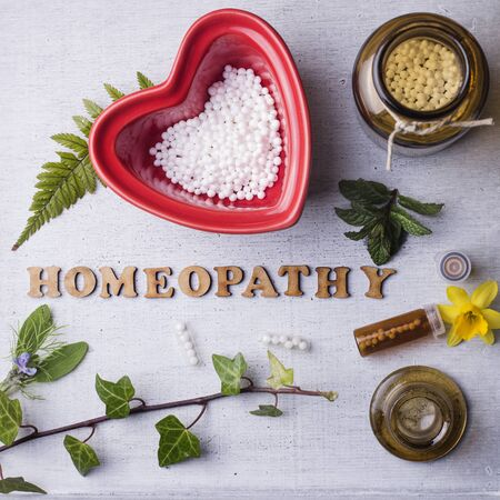 globules: Table with written text Homeopathy, homeopathy globules and bottles. Square format Stock Photo