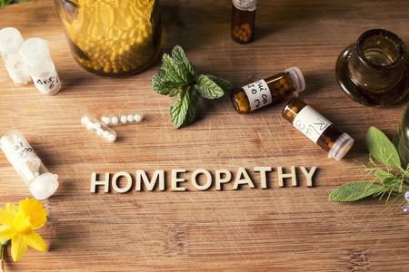 Tabla de texto escrito con la homeopatía, glóbulos de homeopatía y botellas