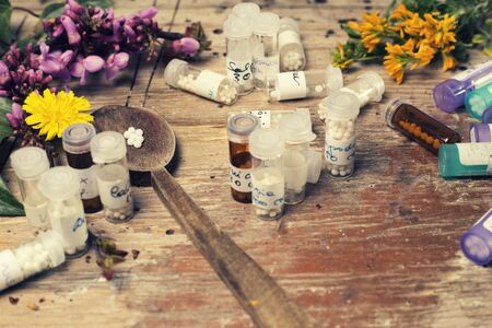 pinks: bottles with homeopathy globules and spoon, decorated with flowers pinks,yellows  and ivy Editorial