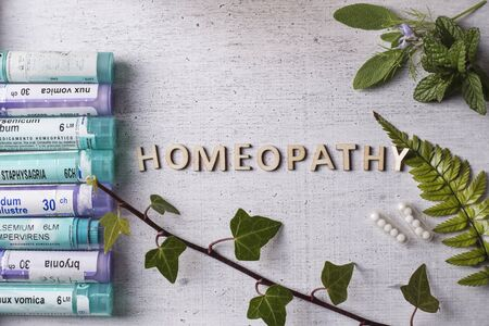 Table with written text Homeopathy, homeopathy globules and bottles Editorial