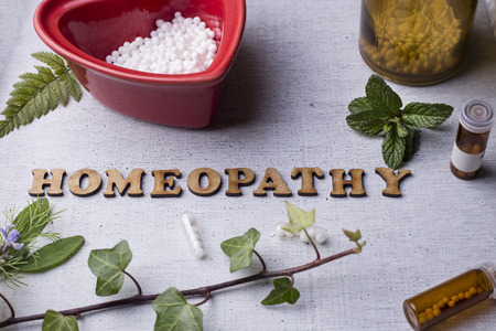 globules: Table with written text Homeopathy, homeopathy globules and bottles Stock Photo
