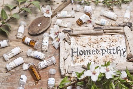 homeopatia: Tabla con el texto escrito a mano homeopatía, glóbulos cuchara de homeopatía y flores