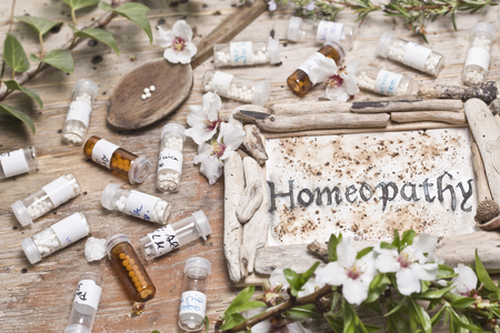 globules: Table with handwritten text  Homeopathy, spoon homeopathy globules and flowers Editorial