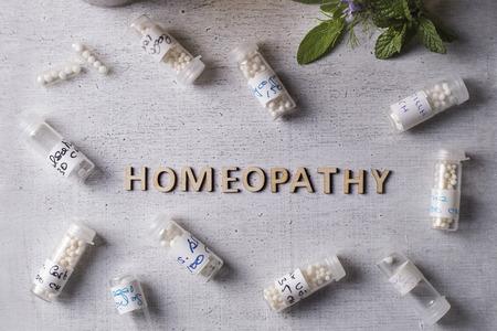 homeopatia: Tabla de texto escrito con la homeopat�a, gl�bulos de homeopat�a y botellas