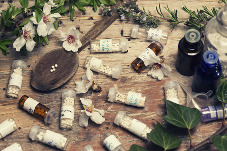 globules: bottles with homeopathy globules and spoon, flowers and ivy