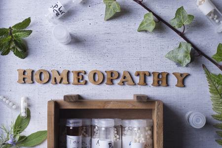 homeopatia: Tabla de texto escrito con la homeopatía, glóbulos de homeopatía y botellas
