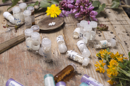 globules: bottles with homeopathy globules and spoon, decorated with flowers