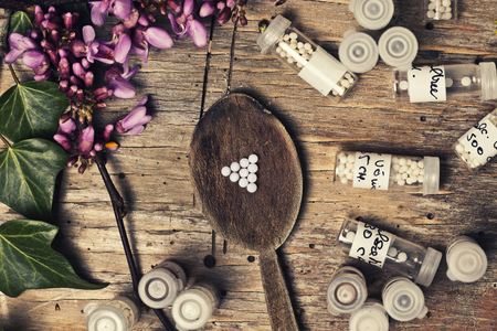 bottles with homeopathy globules and homeopathy liquid and ivy