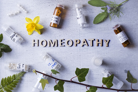 homeopathy: Table with written text Homeopathy, homeopathy globules and bottles Editorial