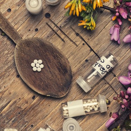 pinks: bottles with homeopathy globules and spoon, decorated with flowers pinks and yellow, square format Editorial