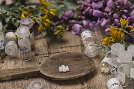 pinks: bottles with homeopathy globules and spoon, decorated with flowers pinks and yellow Editorial