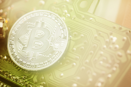 Golden Bitcoin virtual currency coin on a circuit board background