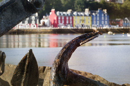 Old anchor with view of Scottish town Tobermory town in the background