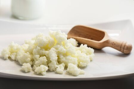 Milk kefir grains in plate and wooden spoon with a glass of kefir in the back, photographed with natural light