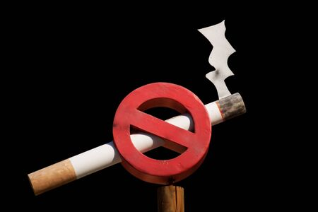 crossed cigarette: Non smoking sign isolated on black