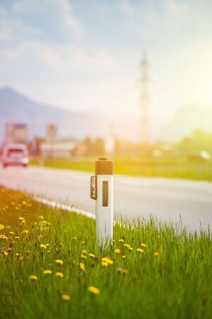 Reflector post and cars at an idyllic asphalted road in summer, flowers and green grass
