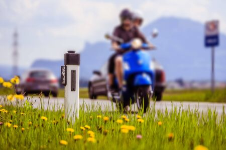Reflector post and a couple on a motor bike at an idyllic asphalted road in summer, flowers and green grass