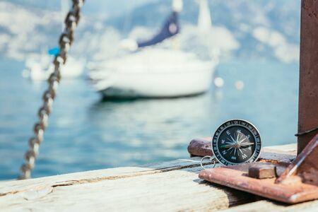 Bussola che giace sul molo di legno in primo piano, barche a vela sullo sfondo sfocato