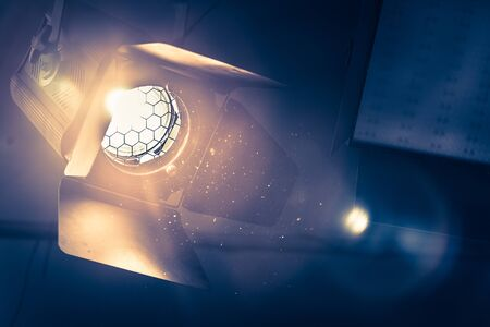 Professional orange studio spotlight hanging on the ceiling. Lighted dust particles and lens flares. Standard-Bild