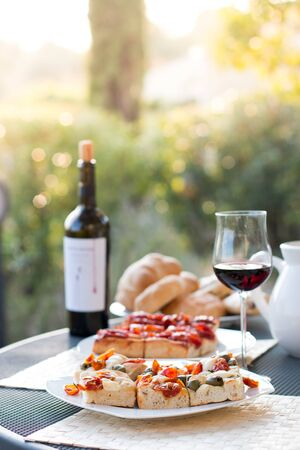 Italian Dinner with red wine, pizza and bread outside. Vacation