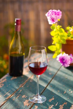 Glass of red wine on an old, rustic wood table. Enjoying it in the own garden in the evening sun.
