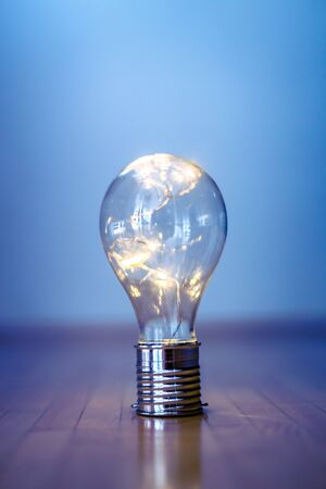 LED light bulb is lying on the wooden floor. Symbol for ideas and innovation. Copy space.