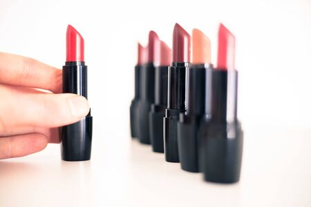 Female hand is taking a colourful red lipstick, elegant cosmetic products