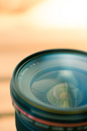 Close up picture of a professional optic photo lens. Smooth blurry background, warm colors.