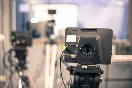 Lens of a film camera in an television broadcasting studio, spotlights and equipment