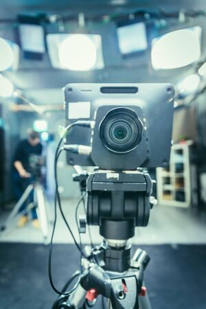 Lens of a film camera in an television broadcasting studio, spotlights and equipment, cameraman in the blurry background