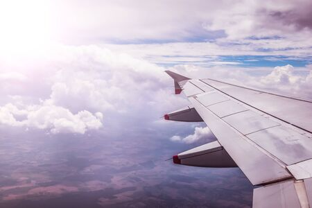 View of a grey airplane wing through the aircraft window. Sunshine, global warming.