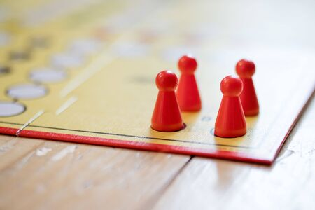 Meeples on a board, ready for playing a parlor game, ludo Stock Photo