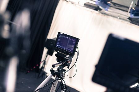 Film camera with lcd screen on a tripod in a television studio