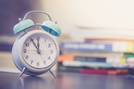Alarm clock is standing on a grey desk, books and office stuff in the blurry background