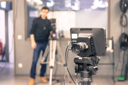 Film camera on a tripod in a television broadcasting studio, cameraman in the blurry background 스톡 콘텐츠